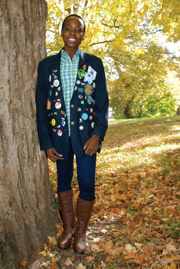 In her senior class photo, Wanzita Ally's jacket features a wide array of buttons and pins and a Rotary patch on the pocket.